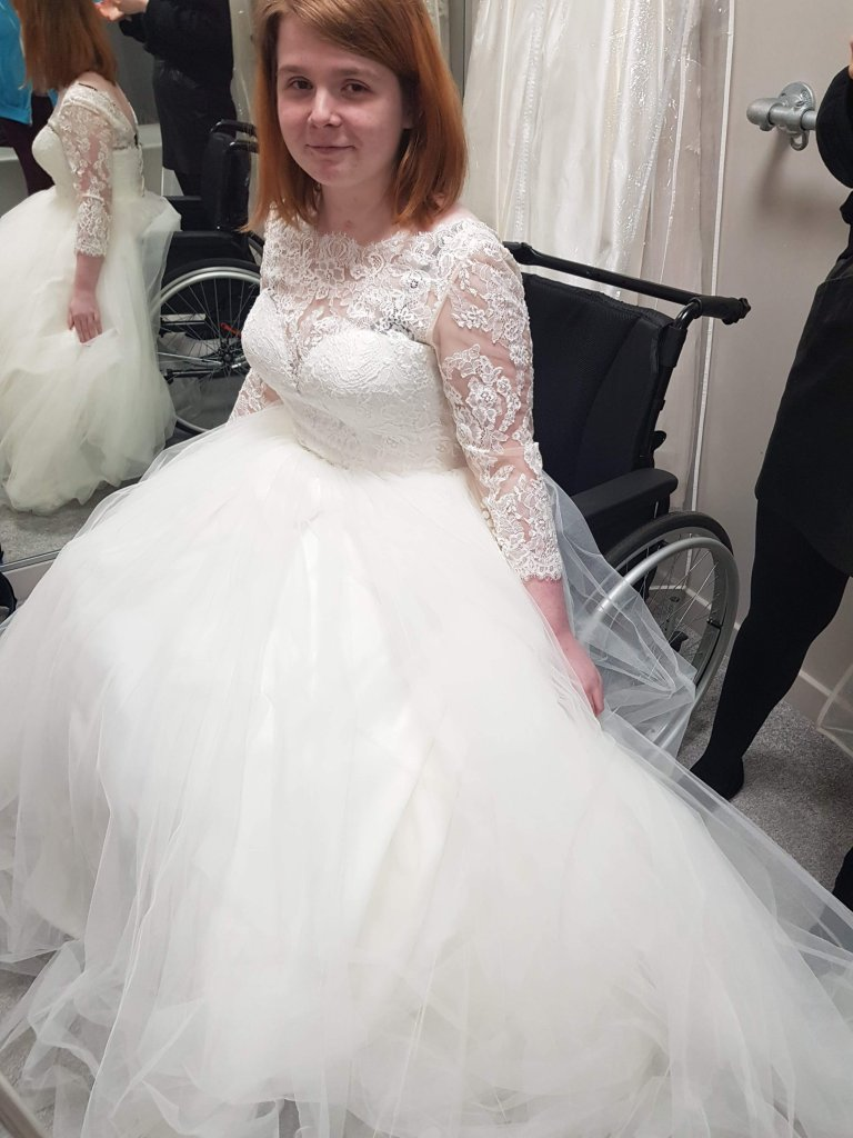Ami is trying on a very big puffy wedding dress. The dress is called Kate, named after the wedding dress that Princess Kate wore on her wedding day. The dress is a similar design.