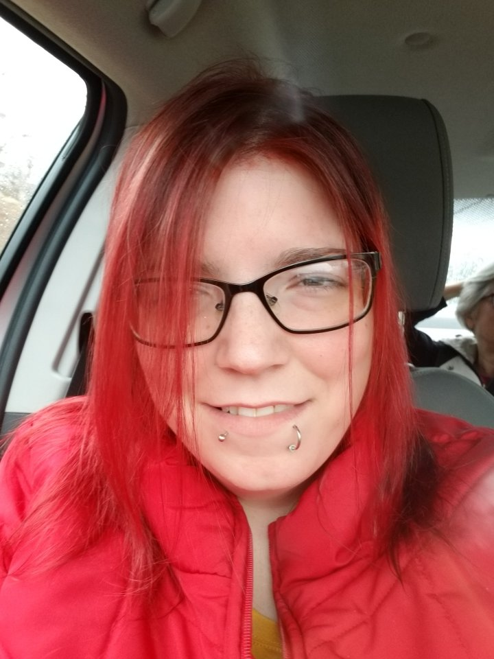 Bethany is smiling at the camera. She has long bright red hair, wearing a red coat and has facial piercings