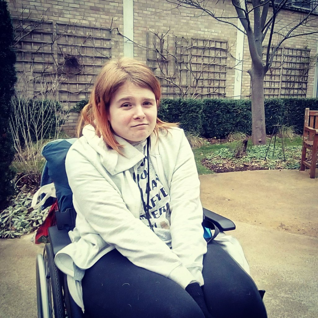 Ami is sitting in her wheelchair, in a small garden at Addenbrooke's hospital.