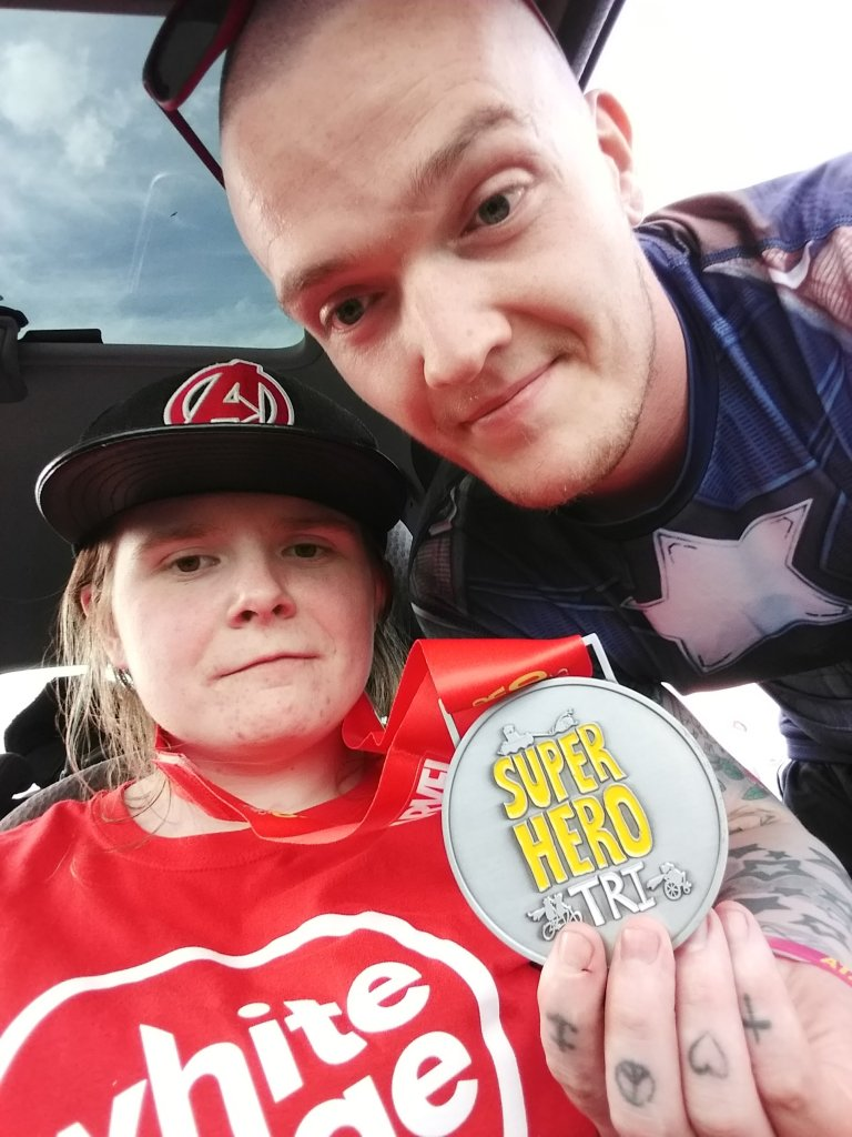 Ami has just transferred into the car after leaving the Superhero Tri. Ewan is beside her, holding up a medal. They look shattered.