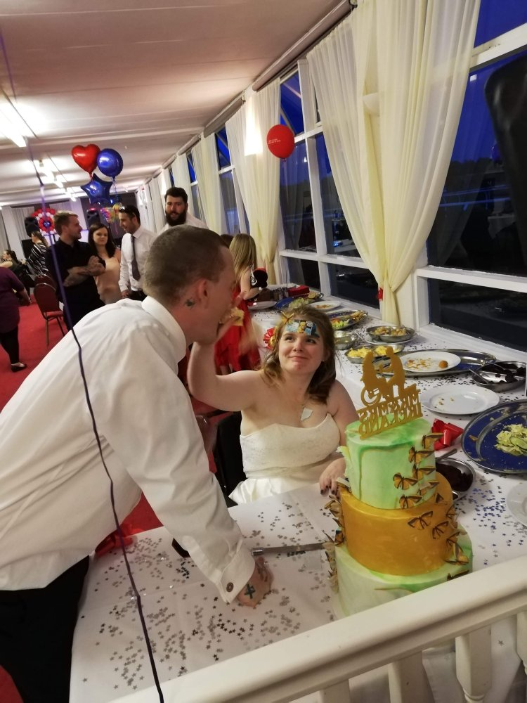 Ami shoving wedding cake in Ewan's face