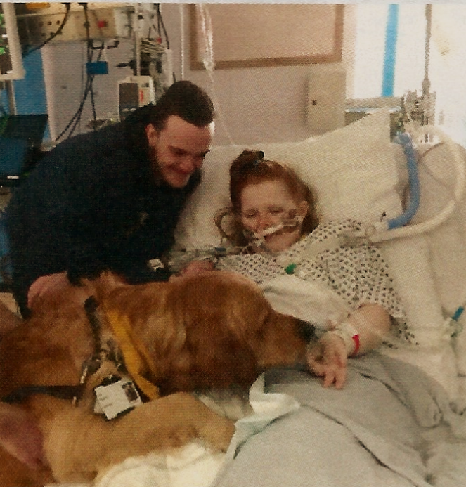Ami is in a hospital bed, critically ill. Ewan is standing by her side as a big support dog has come to see Ami. Various tubes and machines fill the background