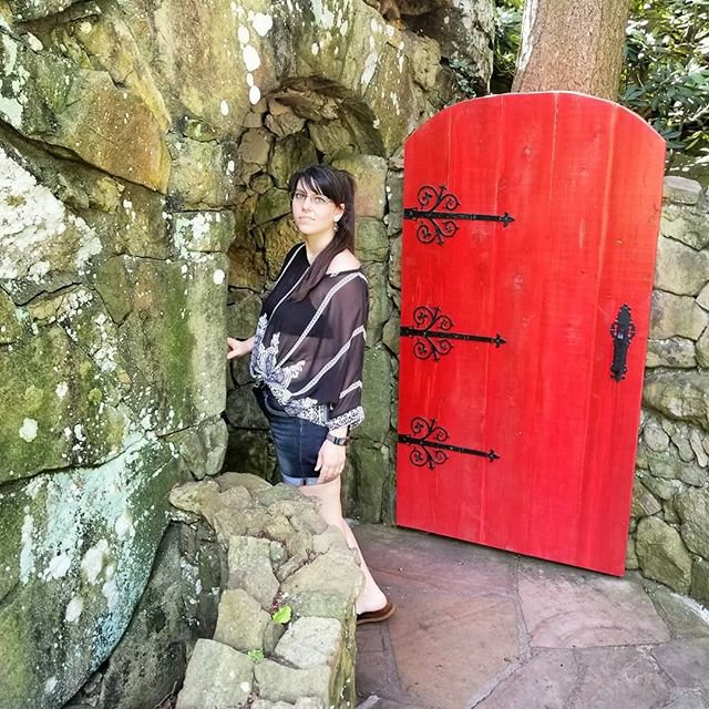 Savannah is standing under an old archway with a big red door opened