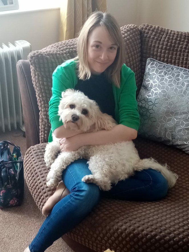 Amy is sitting on a sofa, with a white dog resting on her lap