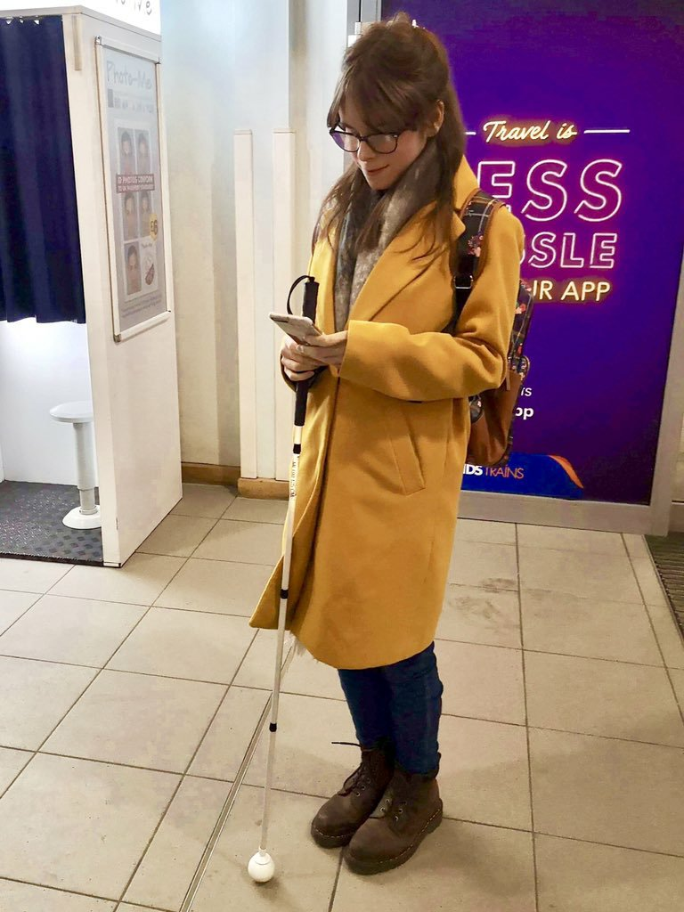 Chloe is wearing a knee-length yellow coat with beige grey scarf and backpack over her left shoulder. Also dark blue denim jeans brown boots. Chloe standing, holding long white cane whilst using phone.