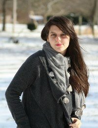 Savannah is smiling, wrapped up in dark grey coat, a light grey scarf in snowy weather