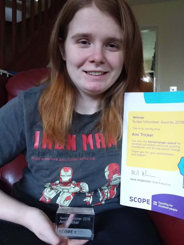 Ami is smiling, holding her award and certificate from Scope