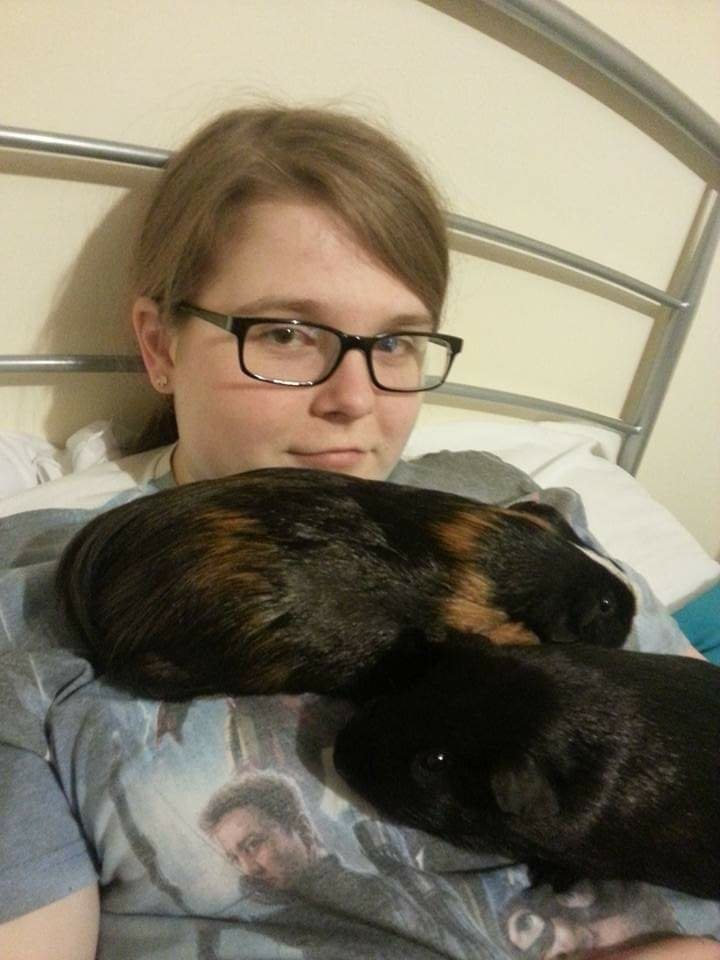Ami on her bed with Loki and Thor resting on her chest.