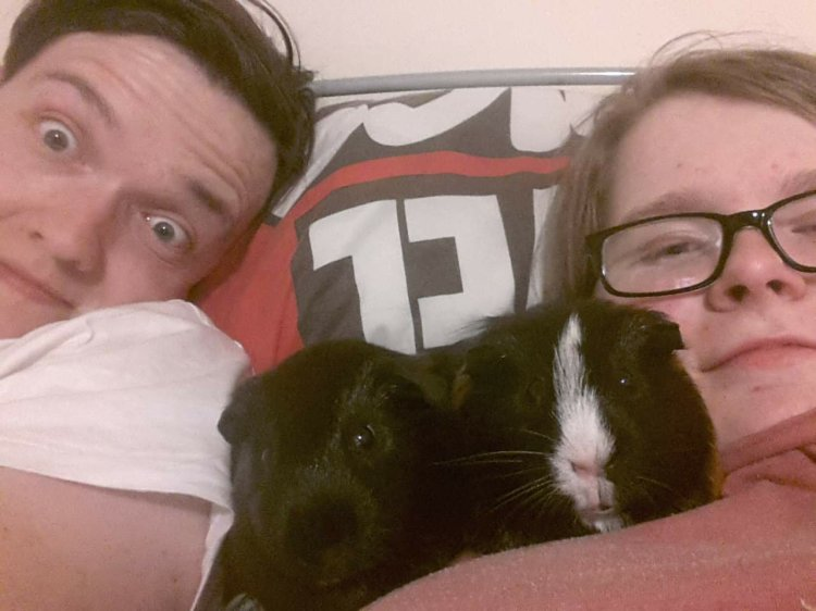 Ewan and Ami on their bed, cuddled up with Thor and Loki in-between them