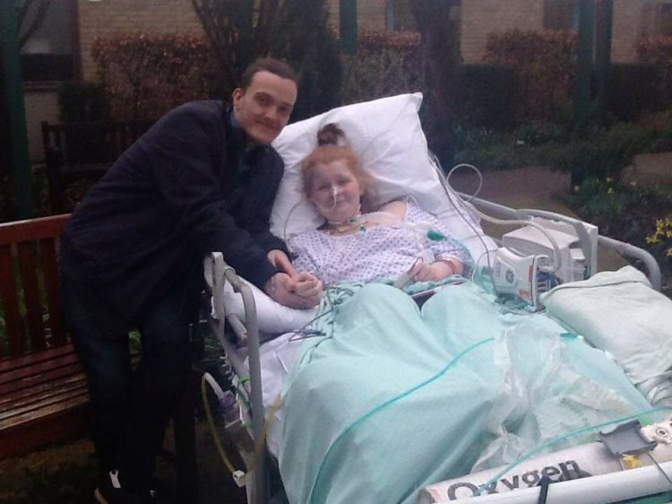 Ami is in a hospital bed, with oxygen tanks, monitors and tubes around her. She is smiling as Ewan is standing beside her, holding her hand