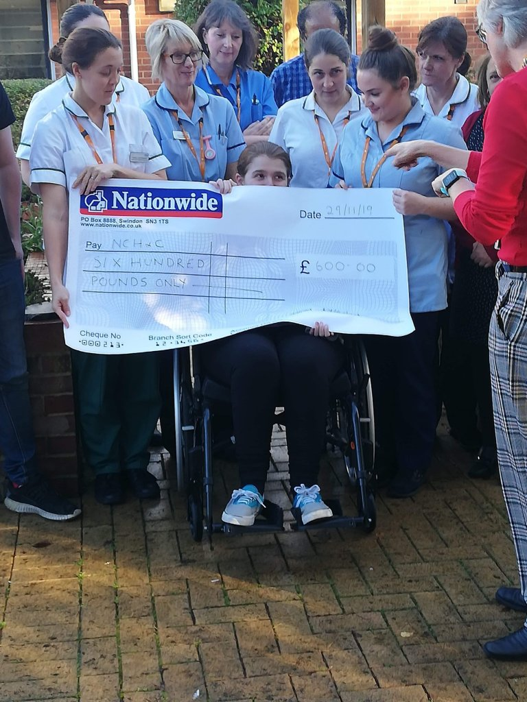 Photo of a big cheque being presented to the unit where Ami received specialist rehabilitation treatment