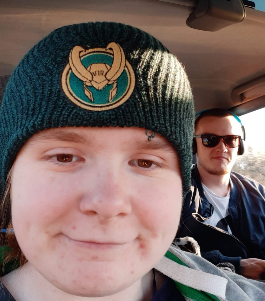 Ami and Ewan are in the car. Ami is wearing her new Loki beanie, which is dark green and has a Loki helmet symbol on the front