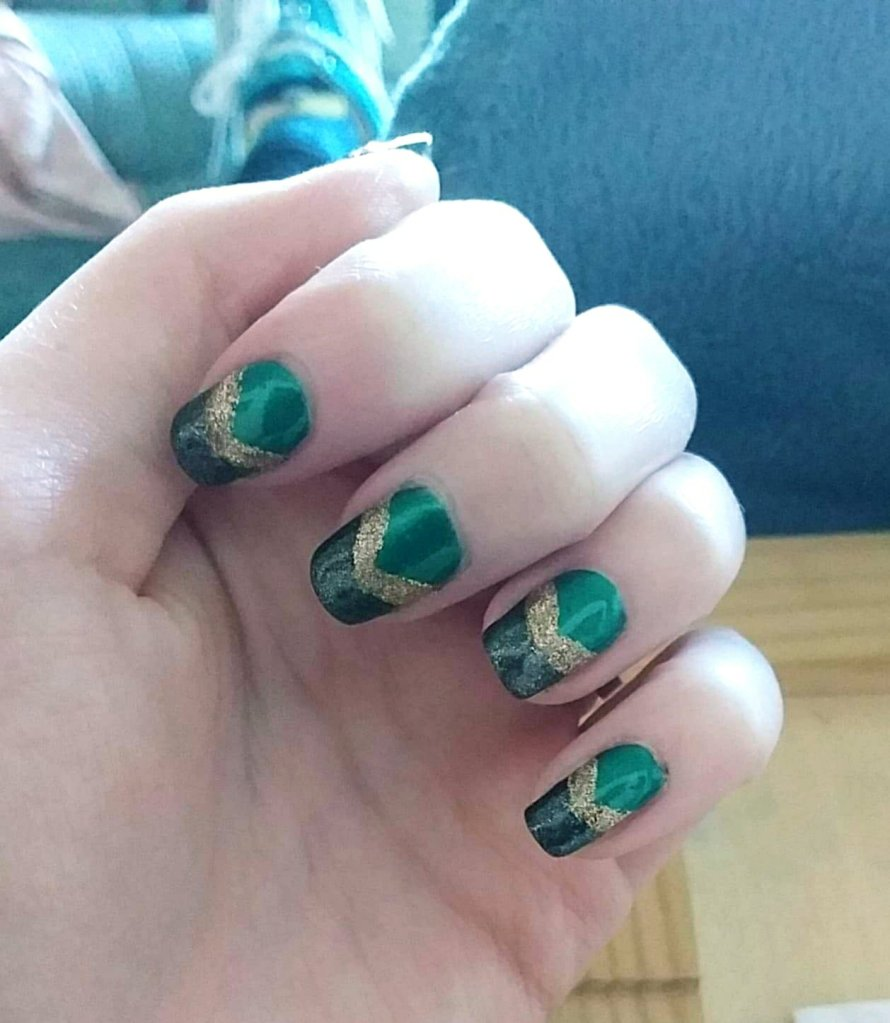 Description of Ami's nail design: the base is dark green,  with sparkly black tips, and sparkly gold arrow heads in between the green and black