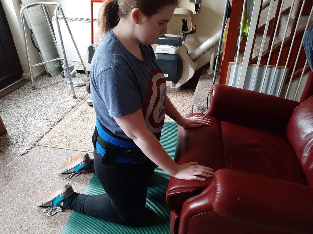 Ami is kneeling on a green yoga/physio mat which is helping her in doing physio at home