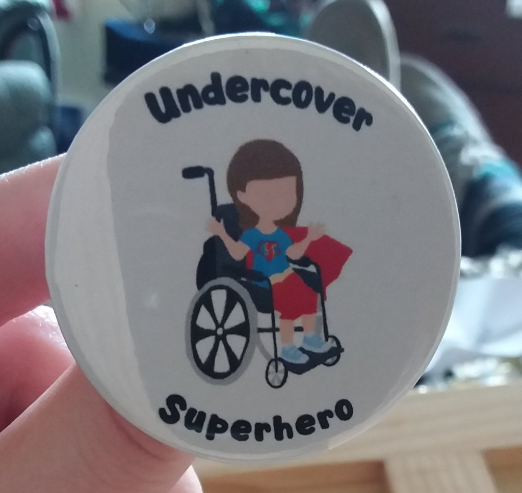 A white badge with the Undercover Superhero badge on