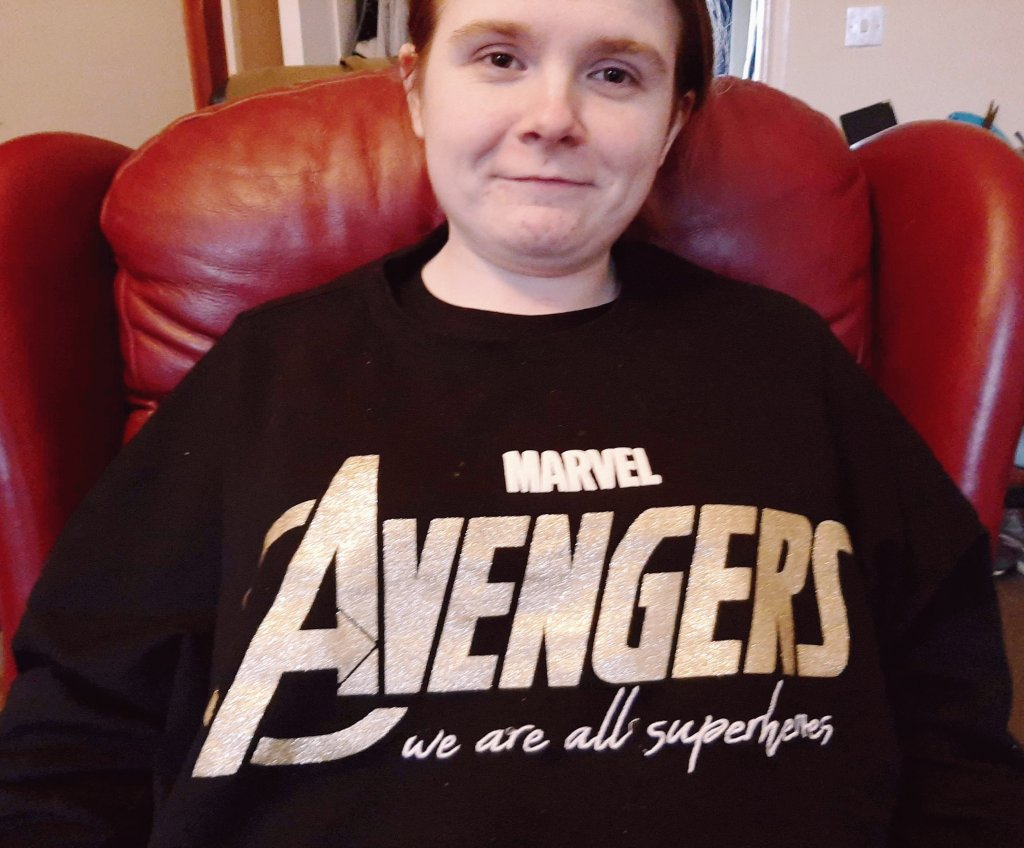 Ami is wearing a black jumper with the Avengers logo in glittery gold, and has the phrase 'we are all superheroes' underneath.