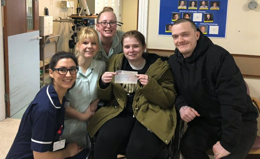 From left to right: West Raynham's ward manager, and 2 healthcare assistants, then Ami and Ewan. We are all smiling as Ami holds a cheque for the physiotherapy department.