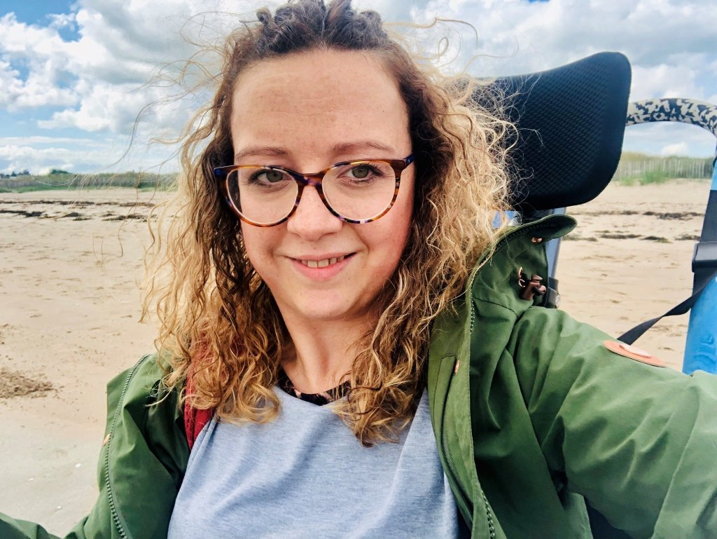 A close up of Carrie-Ann in her wheelchair, at the beach.