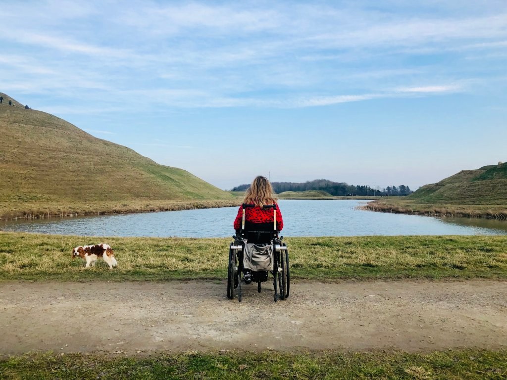 Carrie-Ann is sitting in her wheelchair, with her back to the camera. She is sitting infront of a lake. Her dog is walking on the grass infront of the lake.