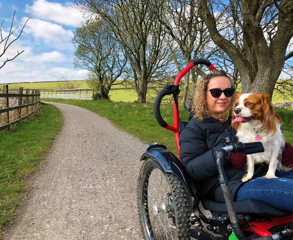 Carrie-Ann is sitting in her Boma 7 All-Terrain wheelchair, with her dog on her lap. They are surrounded by trees and the rolling country hills.
