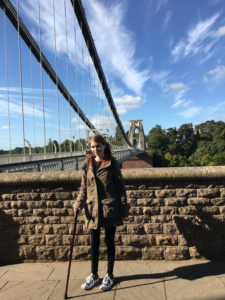 Caz is standing in front of a brick wall, with a long and tall bridge behind. Caz is using a walking stick for support.