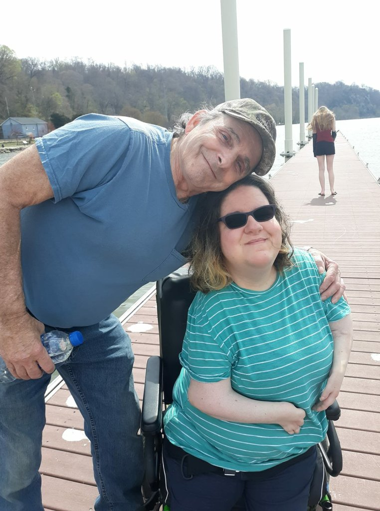 Nikole and her Dad are smiling at the camera. They are on a pier with water stretched in the background.