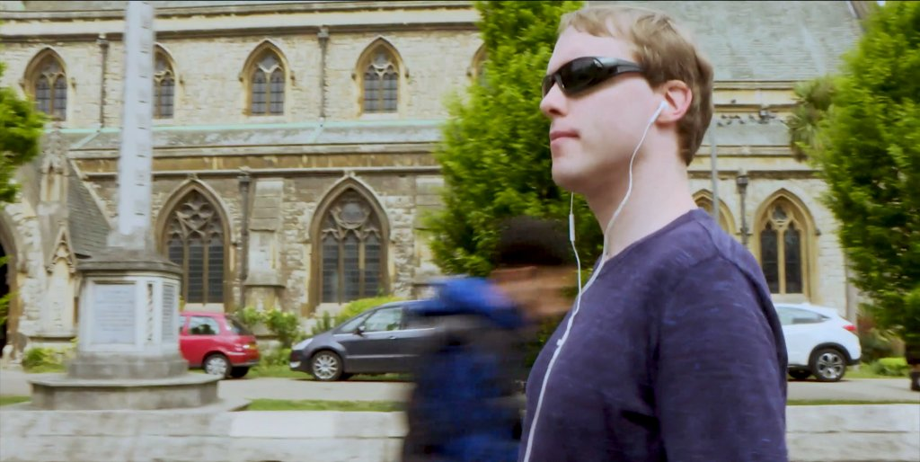 Glen has his side to the camera, he is wearing dark sunglasses and has a pair of white earphones in his ears. A large church/cathedral is in the background. People who are walking past are very blurred.