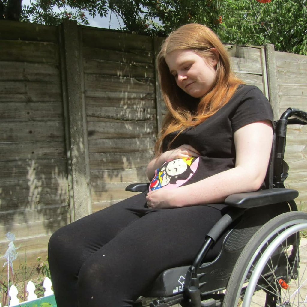 Side view version - Ami is sitting in her wheelchair in the garden. She is wearing a black t-shirt with a Wonder Woman baby design which covers the bump area. Ami is looking down and smiling while cradling bump.