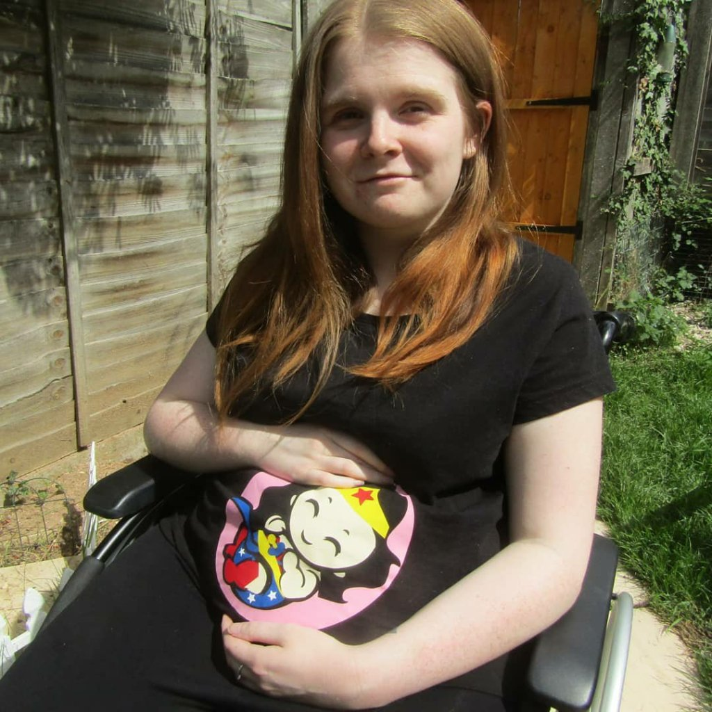 Close up version- Ami is sitting in her wheelchair in the garden. She is wearing a black t-shirt with a Wonder Woman baby design which covers the bump area. Ami is looking at the camera and smiling while cradling bump.
