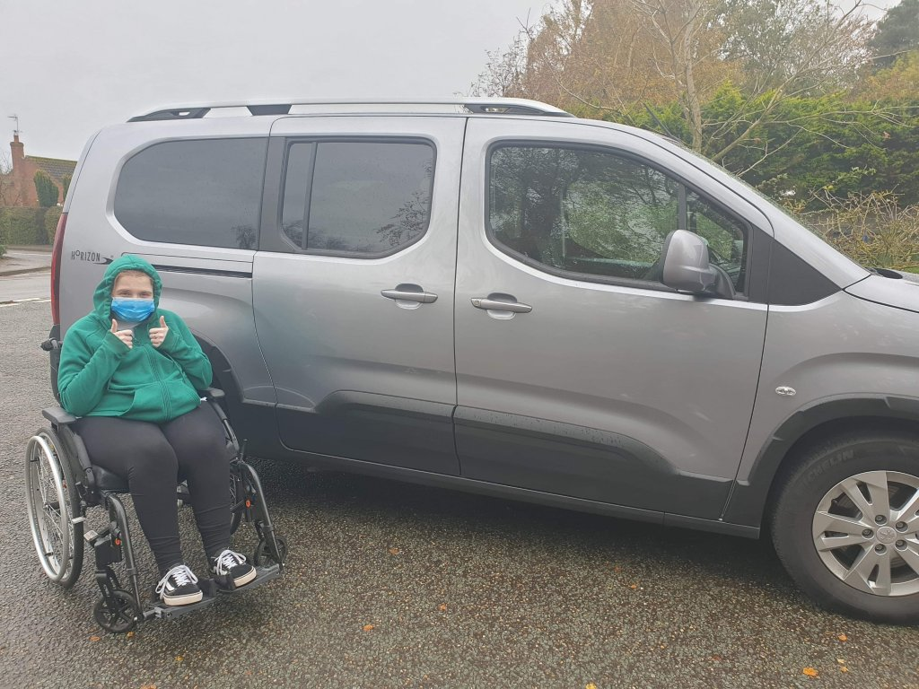 Photo of Ami in her wheelchair, with both thumps up infront of her Motability car