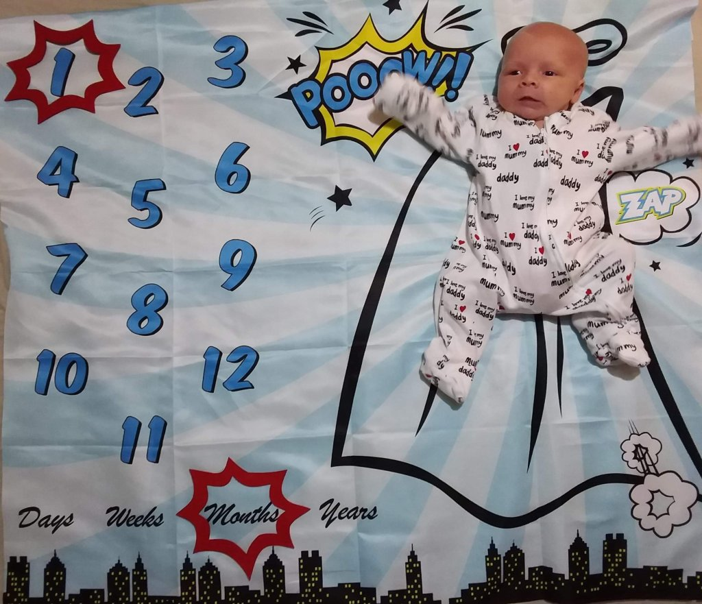Photo of Daisy on her superhero themed milestone blanket with caption shapes around the number 1, and the word months.