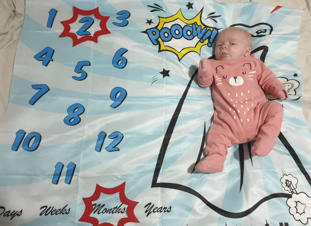 Photo of Daisy on her superhero themed milestone blanket, with a red caption shape around the number 2 and another shape around the word months