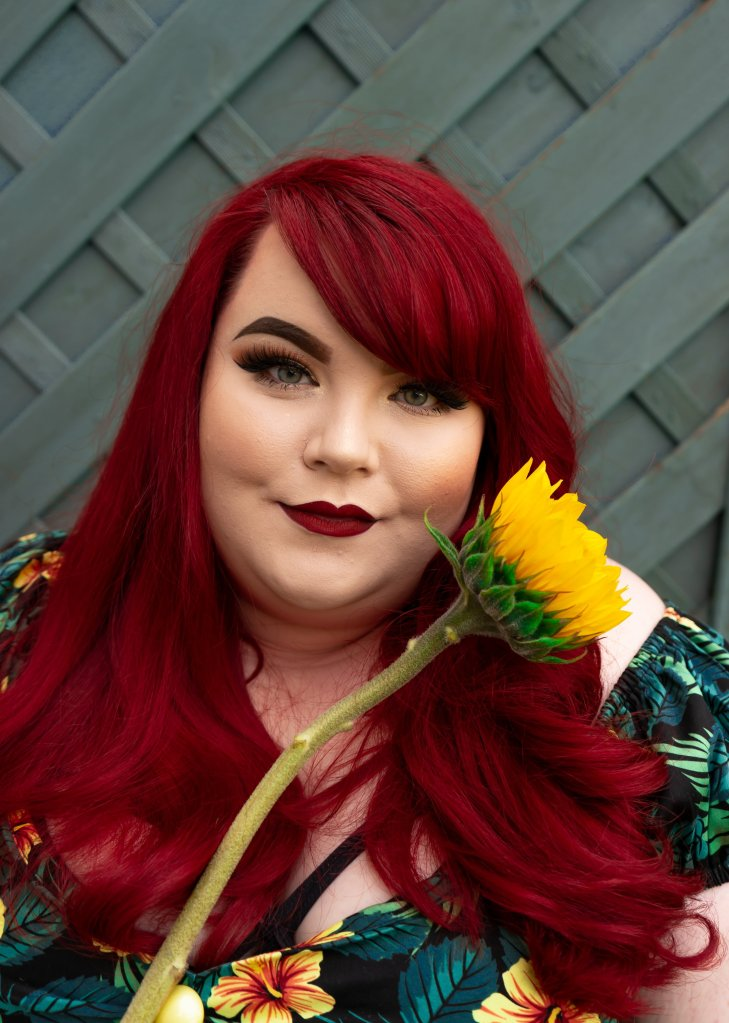 Photo of Georgina, smiling at the camera, and holding a single sunflower