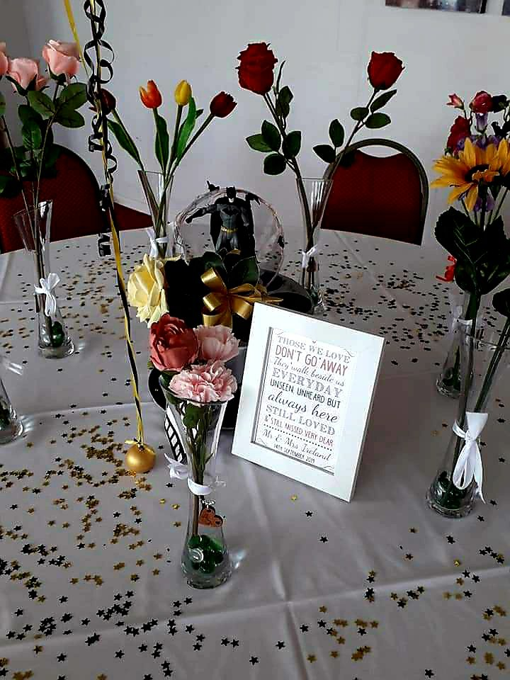 Photo of in memory table, flowers in vases to represent their favourite flowers or colours.