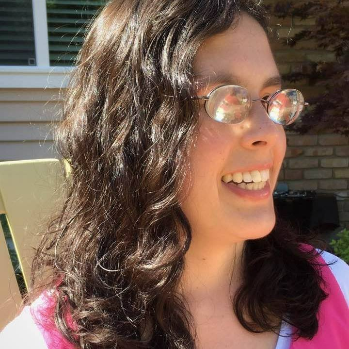 Photo of Macy, at a side angle. She has long dark, wavy hair, is wearing glasses and smiling broadly