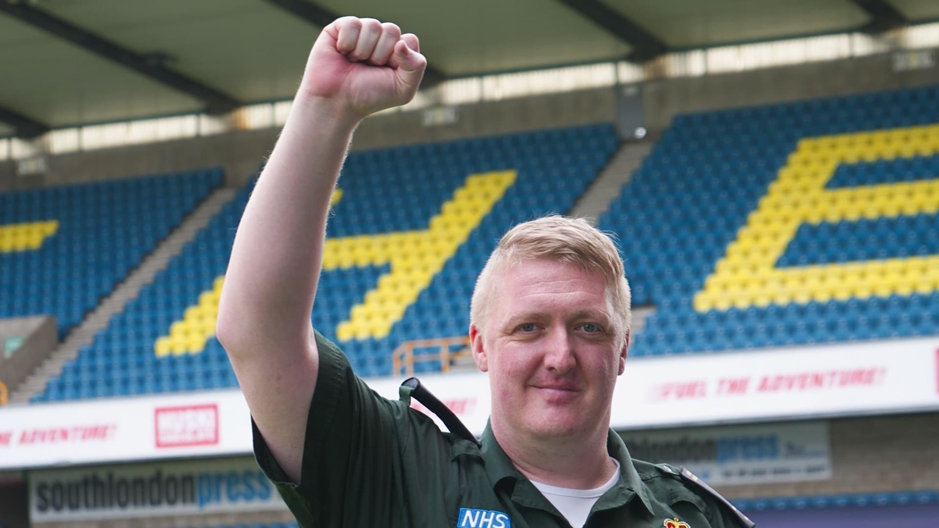 Photo of Sean smiling at the camera, whilst pumping his fist in the air, in front of 'The Den' stands at Millwall Football Club.