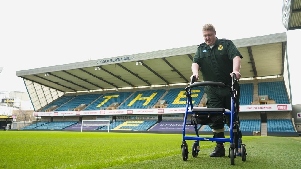 Photo of Sean walking with his rollator,  with 'The Den' stands in the background, at Millwall Football Club.