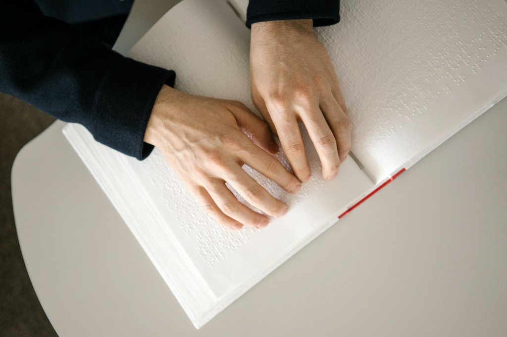 An open book, with a person reading Braille
