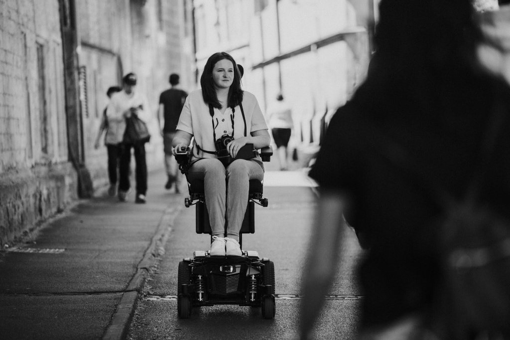 A black and white photo of Shona, in her powerchair with her camera, looking into the distance.