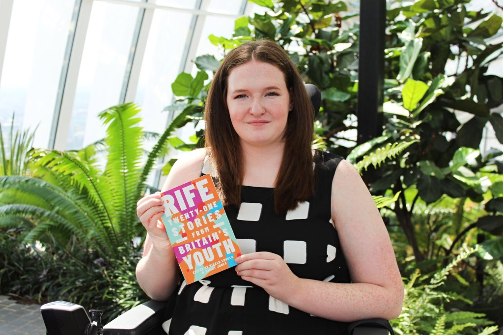 Shona is sitting in her powerchair, smiling at the camera whilst holding a copy of Rife: Twenty-One Stories From Britain's Youth, a book which she featured in. Shona is surrounded by greenery.