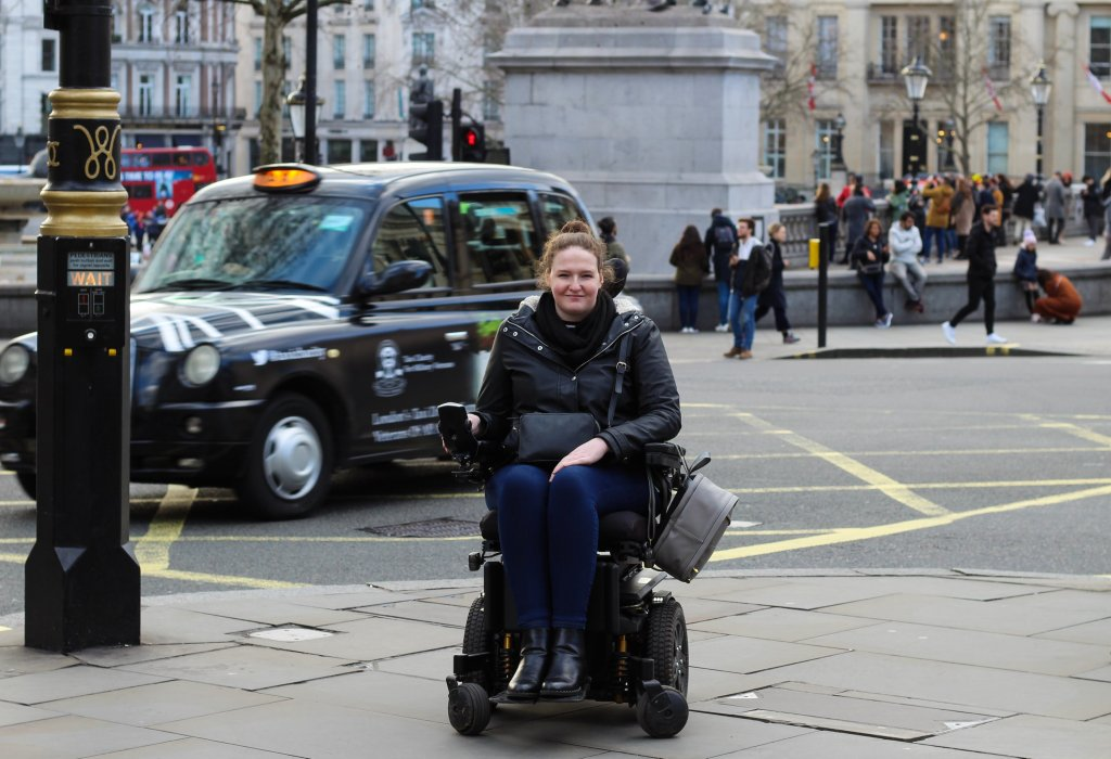 Shona is using her powerchair, and smiling at the camera. There is a black taxi in the background with lots of people too